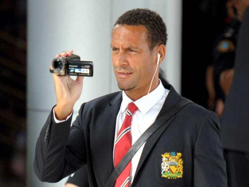 Manchester United player Rio Ferdinand uses a video camera as he arrives at Don Muang International airport in Bangkok ahead of a July 13 friendly against a Thai All-Star XI as the club begins its new era under boss David Moyes. AFP