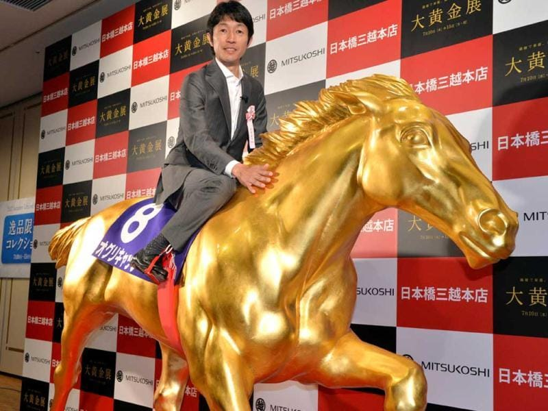 Japanese leading jockey Yutaka Take poses on a life-sized statue of the Japanese legendary Oguri Cap horse displayed at the opening of the Gold Expo event at Tokyo's Mitsukoshi department store. AFP
