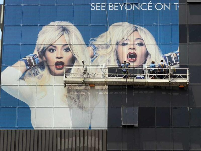 Workers cover glass windows of a highrise building in Hollywood with advertising for the current tour by popstar Beyonce in Hollywood, California. AFP