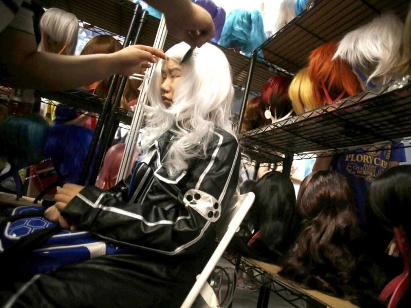 A costumed visitor is helped to wear a wig at a wig shop during the China International Comics and Games Expo in Shanghai, China. AP Photo