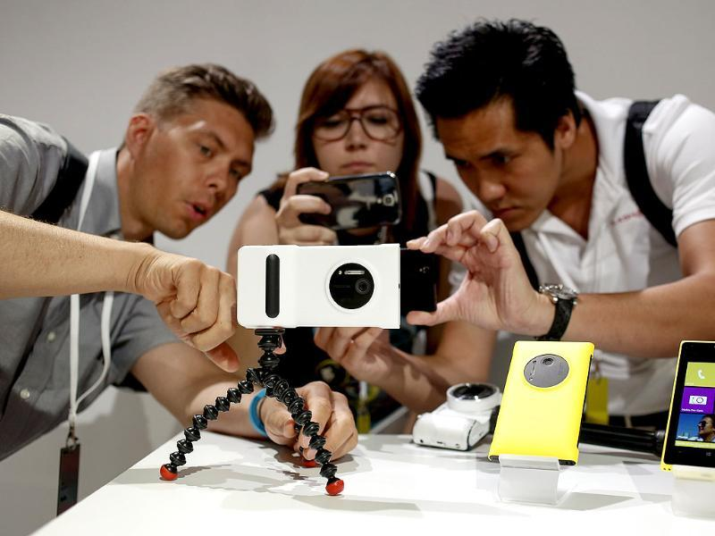 Guests at Nokia's unveiling of its new Lumia 1020 smartphone use the new phone's 41-megapixel camera with a grip in New York. Photo: Reuters/Shannon Stapleton
