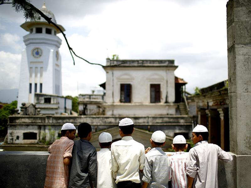 Nepalese Muslim boys look out from the roof of a mosque as they wait to offer Friday prayers during the Muslim holy month of Ramadan in Kathmandu. Reuters