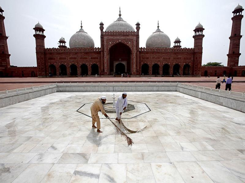 Workers clean the floor of the Badshahi Mosque ahead of the holy month of Ramadan in Lahore. Reuters