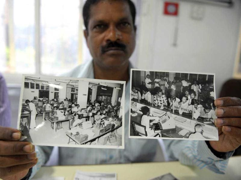 Telecom supervisor, RG Vijay Kumar, shows the photographs taken in 1980 of old system of working telegrams at telegraph office in Hyderabad. (AFP Photo)
