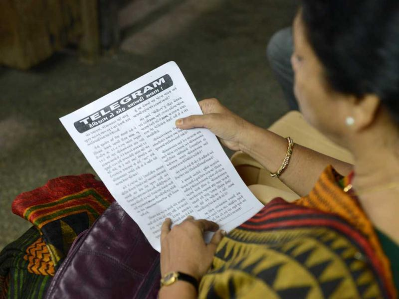 A staff member reads a telegram printed in Gujarati as she participates in a function to bid farewell to telegraphic services at the Central Telegraph Office in Ahmedabad. (AFP Photo)