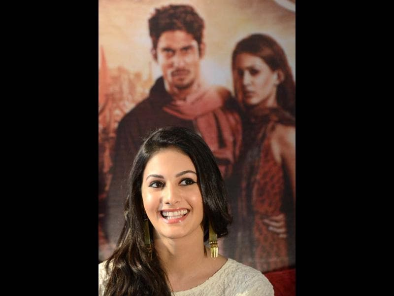 Amyra beside the poster