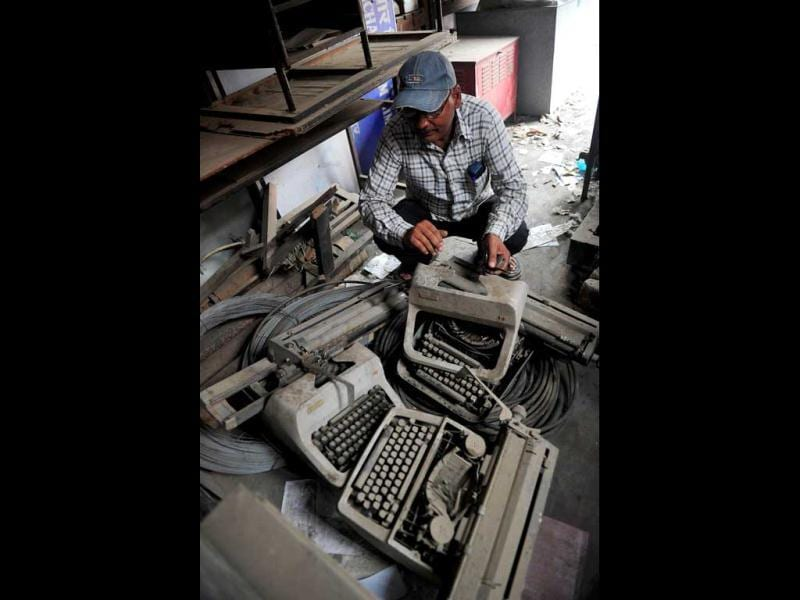 An employee looks at old typewriters laying in a store room at the Targhar telegraph office in Allahabad. (AFP Photo)