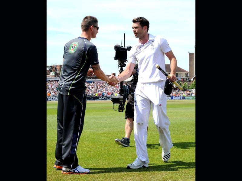 England's James Anderson (R) shakes hands with Australia's captain Michael Clarke after England's narrow victory over Australiain the first Ashes Test match at Trent Bridge. (AFP Photo)