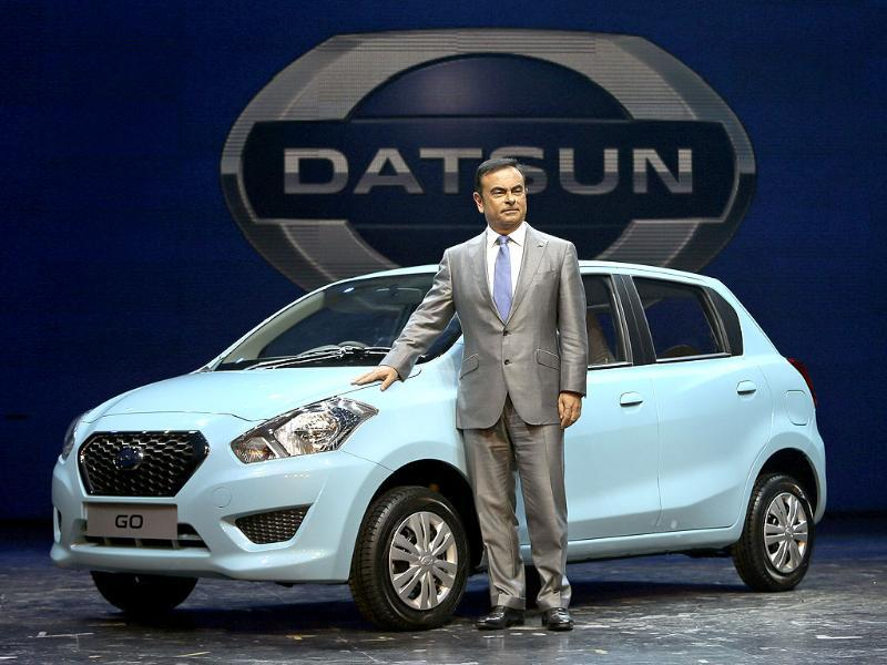 Nissan Motor Co. President and CEO Carlos Ghosn poses with Datsun Go - a five-seat hatchback - during its global launch in New Delhi. It will go on sale in India next year. (AP Photo)