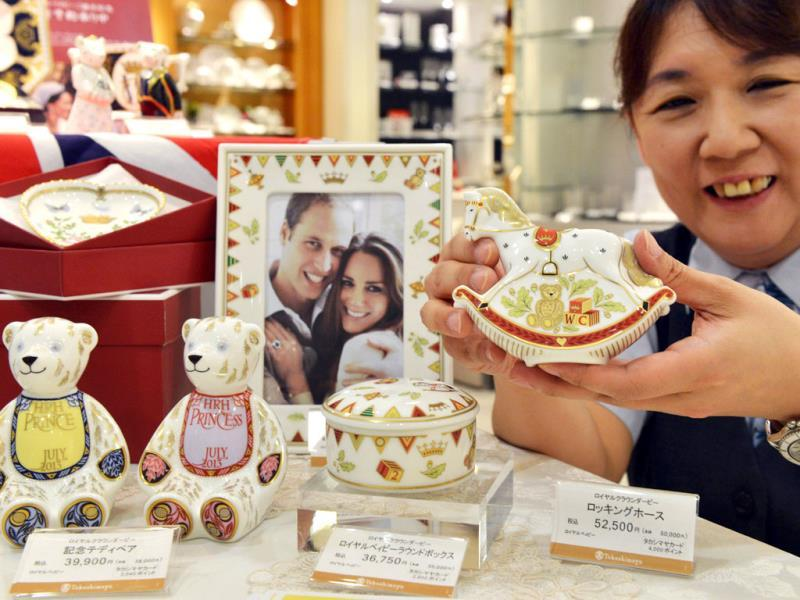 Japan's Takashimaya department store employee displays samples of commemorative figures and table wears for Britain's expected royal baby at a shop of British porcelain maker Royal Crown Derby in Tokyo. (AFP Photo)