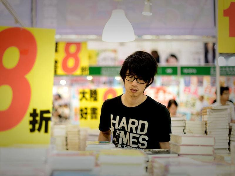 A man looks at books displayed at the Hong Kong Book Fair. The fair opened as tens of thousands of book lovers expected to flock to the seven-day annual event. Photo: AFP / Philippe Lopez