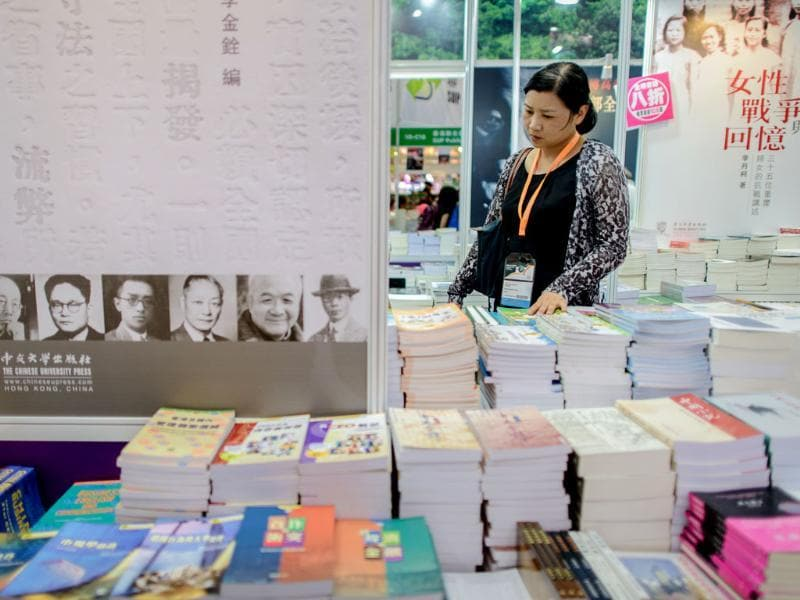 A woman browses books displayed at the Hong Kong Book Fair on July 17, 2013. Photo: AFP / Philippe Lopez