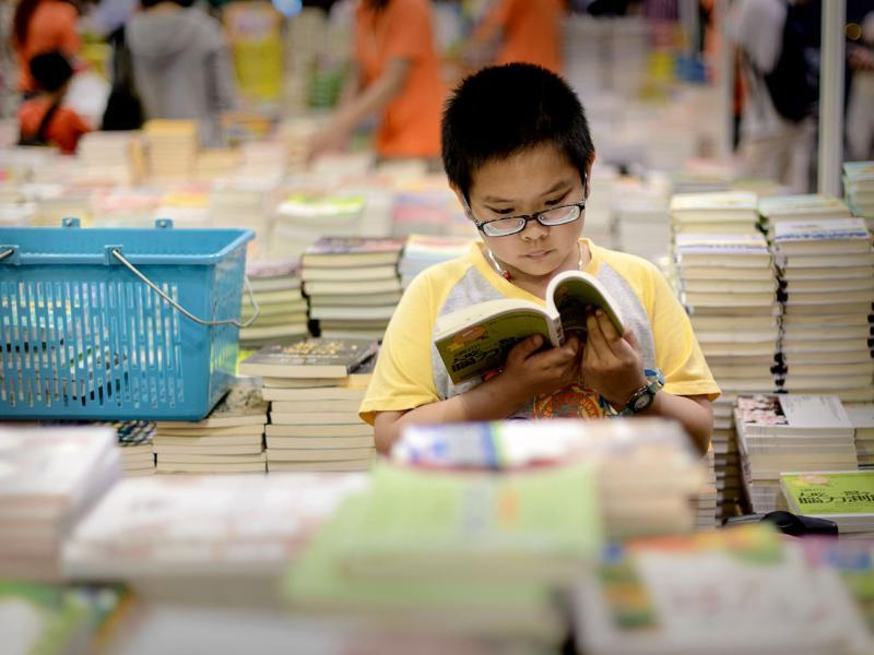 A boy reads a book at the Hong Kong Book Fair. Photo: AFP / Philippe Lopez