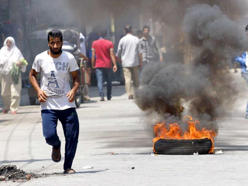 Kashmiris run past a burning tyre during a protest against the killing of villagers by Border Security Force soldiers in Srinagar. (HT Photo/Waseem Andrabi)