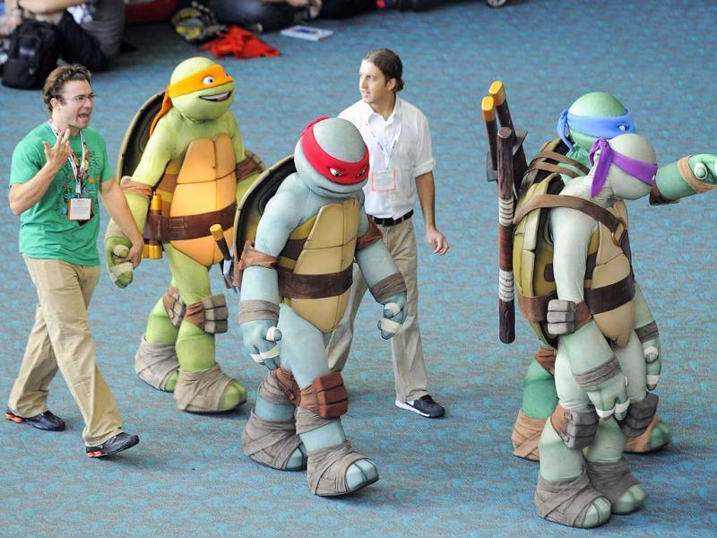 Teenage Ninja Turtle characters walk through the San Diego Convention Center during the preview might event on day 1 of the 2013 Comic-Con International Convention in San Diego. (AP Photo)