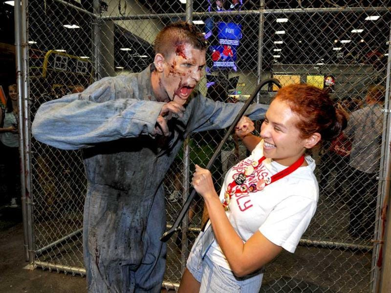 Olivia D'Agostino pulls a away from a zombie at AMC's Walking Dead booth during the preview night event on day 1 of the 2013 Comic-Con International Convention in San Diego. (AP Photo)