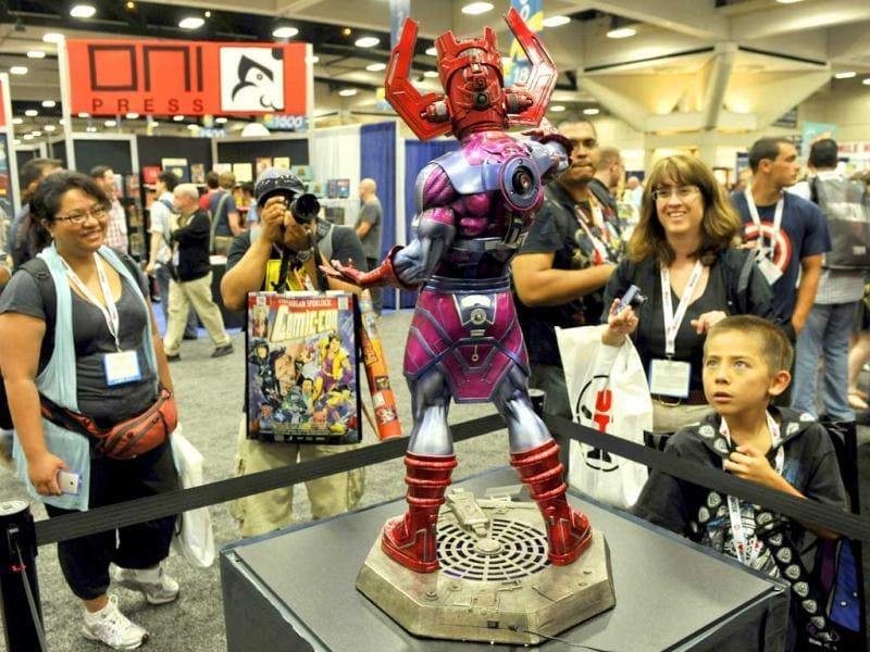 Comic-Con attendees look at a Galactus model during the preview night event on day 1 of the 2013 Comic-Con International Convention in San Diego. (AP Photo)