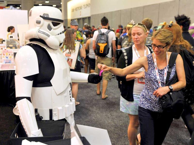 A Star Wars stormtrooper character hands out free bracelets to Comic-Con attendees at the preview night event on day 1 of the 2013 Comic-Con International Convention in San Diego. (AP Photo)