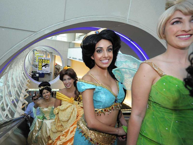 Fans dressed as Disney princesses ride the escalator as they get their credentials during the preview night event on day 1 of the 2013 Comic-Con International Convention in San Diego. (AP Photo)
