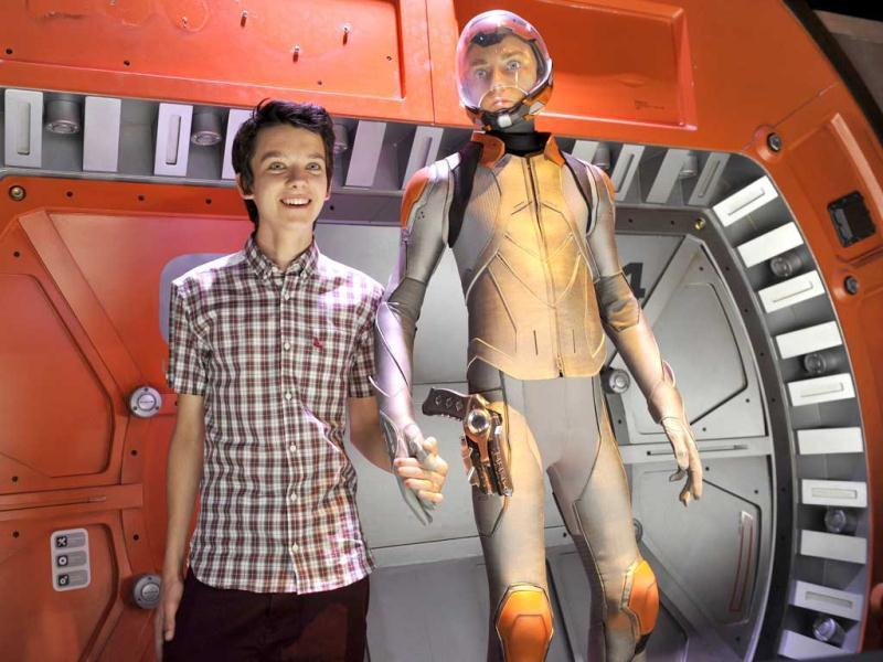 Asa Butterfield, a cast member in the forthcoming film Ender's Game, poses alongside a model of his character in the film at a preview event for the film at the 2013 Comic-Con International Convention in San Diego. (AP Photo)