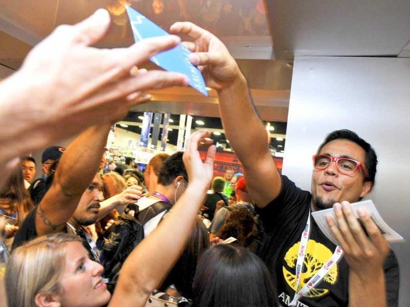 Gilberto Vera of Summit Entertainment hands out free passes to see the premiere of the forthcoming film Escape to Comic-Con attendees in San Diego. (AP Photo)
