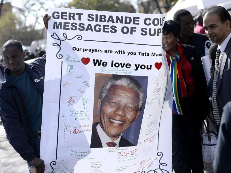 People hold on a poster bearing a portrait of former South African president Nelson Mandela to wish him a happy birthday outside the Medi Clinic Heart Hospital in Pretoria. AFP photo