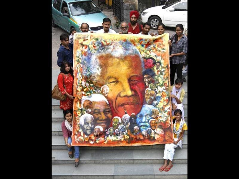 Artists of health education & environment awareness society pose with the painting of former South African president Nelson Mandela in New Delhi on his birthday. HT Photo/Virendra Singh Gosain