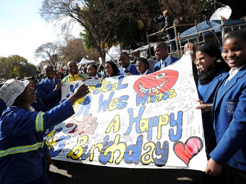 School children hold a banner with messages for the birthday of former South African president Nelson Mandela holding a banner on outside the Medi Clinic Heart Hospital in Pretoria. AFP photo
