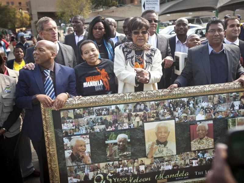 Nelson Mandela's ex-wife Winnie Madikizela-Mandela stand by a montage of photos of the former South African president inside the gate of the Mediclinic Heart Hospital where he is is being treated in Pretoria, South Africa. AP Photo