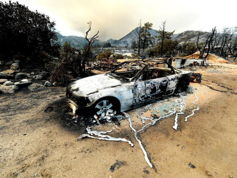A burned-out BMW car next to a destroyed home after a massive wildfire scorched parts of Idyllwild in California. (AFP Photo)