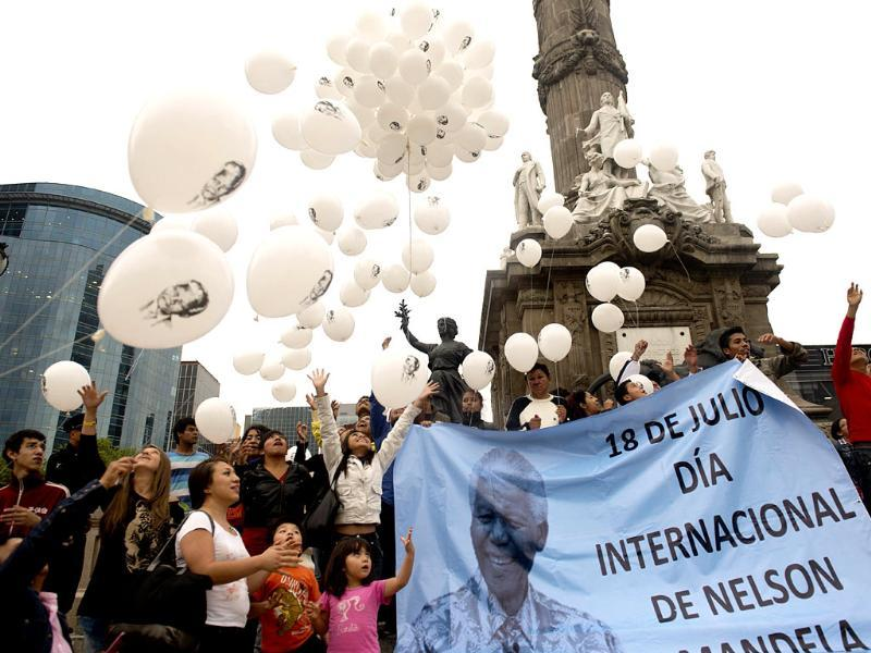 People release balloons with an image of former South African President Nelson Mandela to mark Nelson Mandela International Day at Independence Angel square in Mexico City. (AFP Photo)