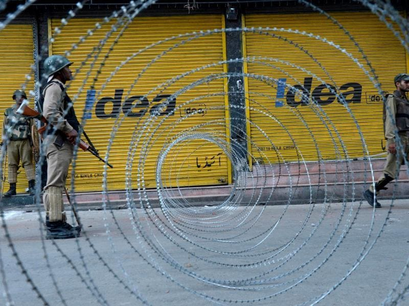 An Indian paramilitary troop stands guard near a barbed wire fence during a curfew imposed in Srinagar. (AFP Photo)