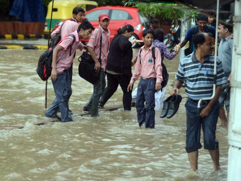 School children try to cross a flooded street in New Delhi following heavy showers. (AFP Photo)