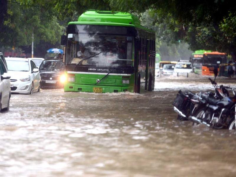 A bus tries to cross a water logged street during a heavy downpour in New Delhi. (AFP Photo)
