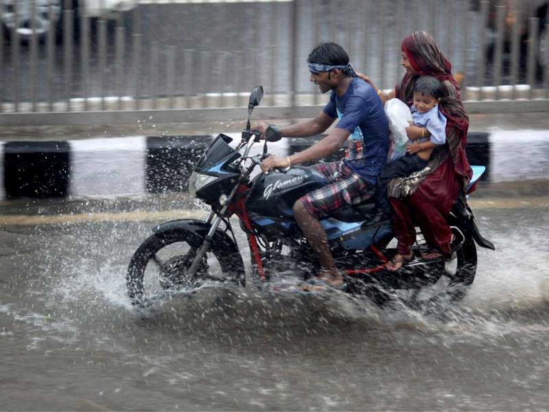 A motorcyclist wades through a waterlogged road after a heavy shower in New Delhi. (PTI Photo)