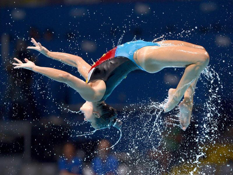 A swimmer from the Italian team is airborne as they perform their routine in the synchronised swimming free combined event at the FINA Swimming World Championships in Barcelona, Spain.(AP Photo)