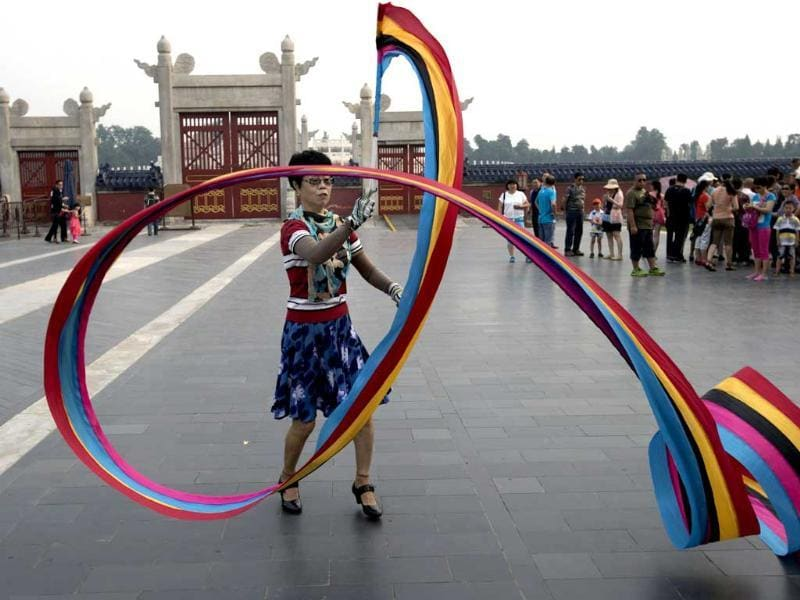 A Chinese woman exercises by twirling a color ribbon at a park in Beijing, China. AP Photo