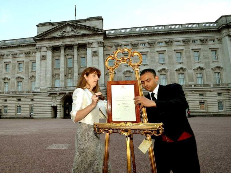 The press secretary to Britain's Queen Elizabeth, Ailsa Anderson, and footman Badar Azim, place a notice formally announcing the birth of a son to Prince William and Catherine, Duchess of Cambridge, in the forecourt of Buckingham Palace, in central London. (Reuters)