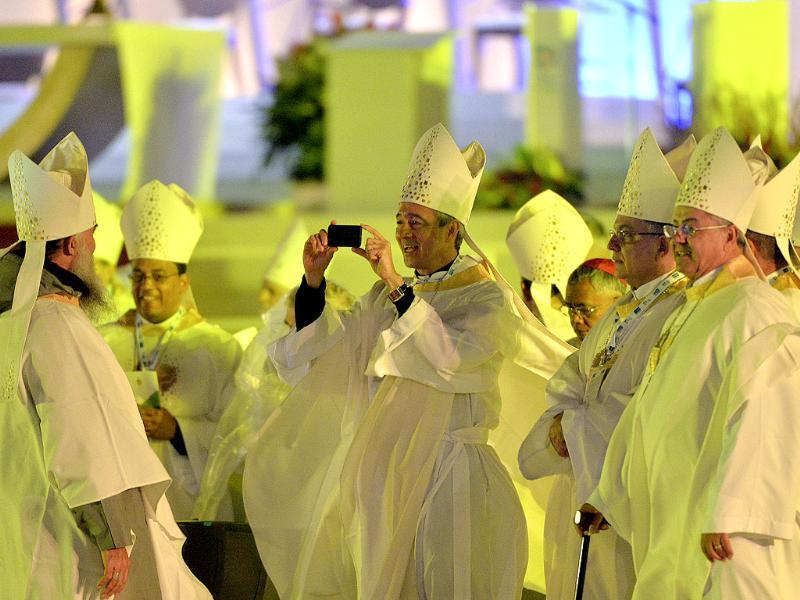 A member of the clergy takes a picture near a newly constructed altar on Copacabana beach, where pilgrims gathered for the World Youth Day inaugural Mass in Rio de Janeiro. AP