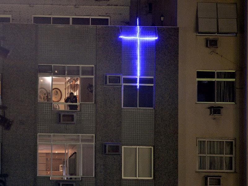 A cross is illuminated on a building near Copacabana beach where pilgrims gathered for the World Youth Day inaugural Mass in Rio de Janeiro. AP Photo