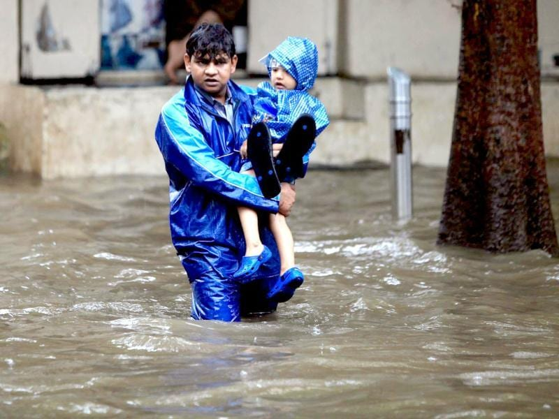 A man carries a child through a flooded street during rain showers in Mumbai. (PTI Photo)