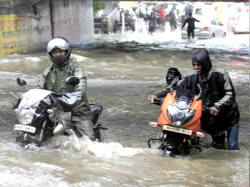 People drive through a flooded street during heavy rains in Mumbai. (Satish Bate/HT)