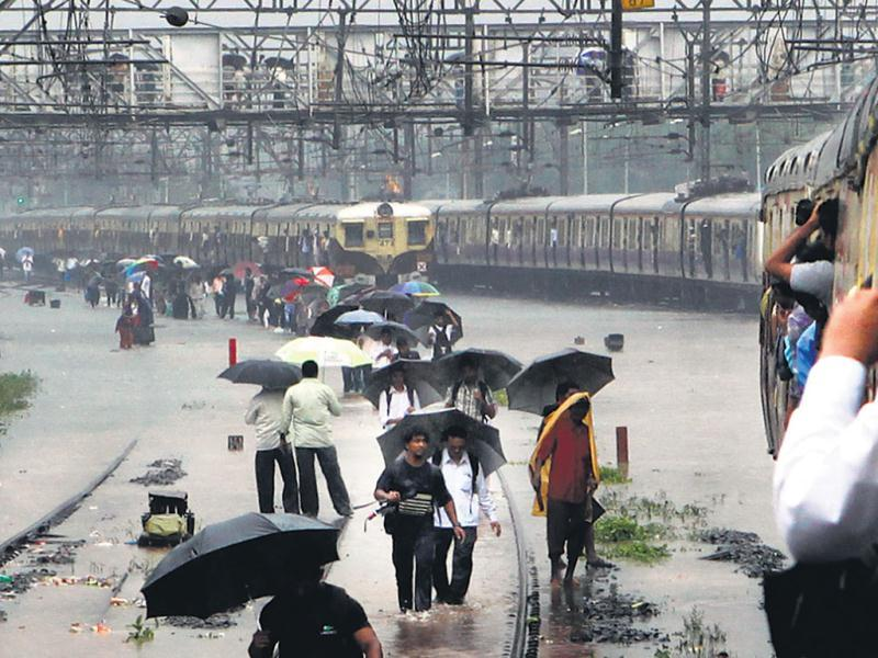 Commuters walk on tracks that were flooded between Kurla and Sion stations. Train services in Mumbai were hit on Tuesday owing to the heavy rain. (HT/Santosh Harhare)