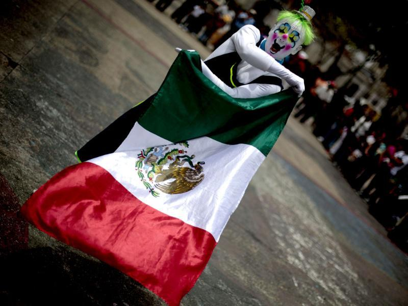 A clown holds a Mexican Flag during a parade to inaugurate the 5th Annual Clowns' Convention in Guatemala City. Reuters
