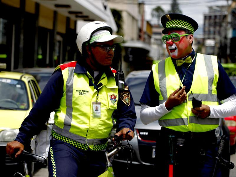 A transit police agent is spoken to by a clown (R) dressed like him during a parade to inaugurate the 5th Annual Clowns' Convention in Guatemala City. Reuters