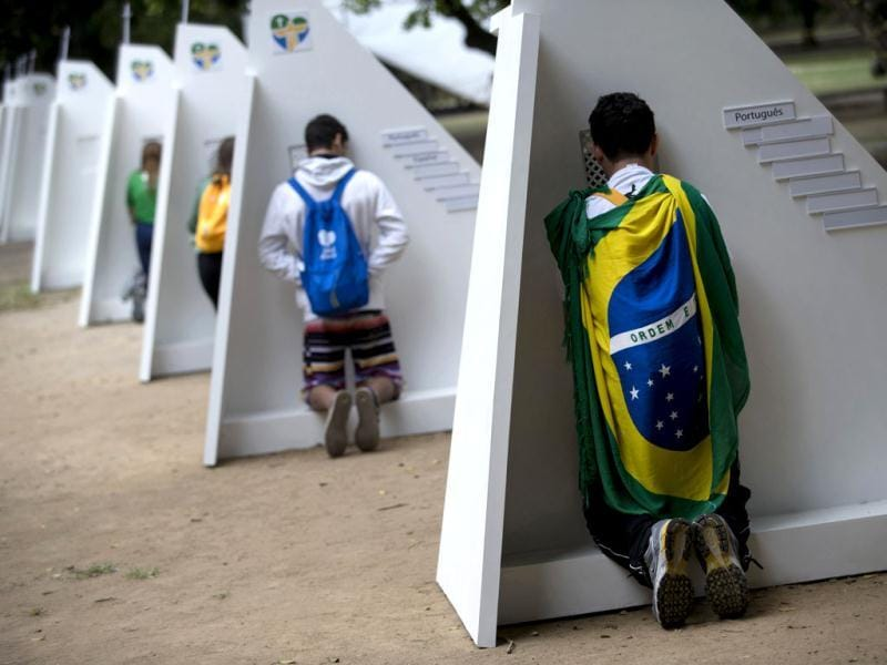 Catholics kneel at portable confessionals set up in Quinta da Boa Vista park during World Youth Day events in Rio de Janeiro, Brazil, Tuesday, July 23, 2013. As many as 1 million young people from around the world are expected in Rio for the Catholic youth event. (AP Photo)