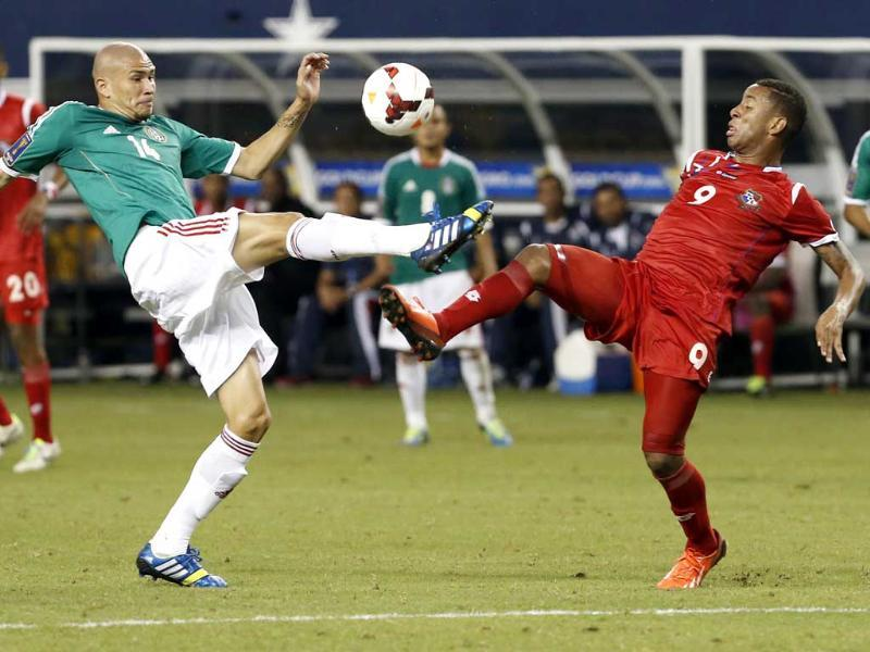 Mexico's Jorge Enriquez (14) and Panama's Gabriel Torres (9) battle for possession of the ball in the second half of the Gold Cup semifinals at Cowboys Stadium in Arlington, Texas. Panama won 2-1. (AP Photo)