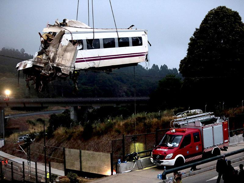 A crane removes a carriage from the tracks at the site of a train crash near Santiago de Compostela, northwestern Spain. REUTERS