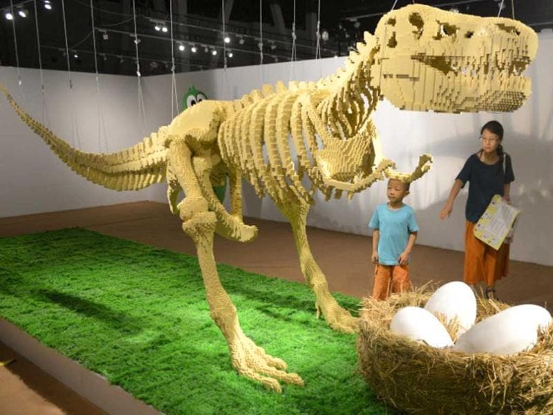 Visitors look at a dinosaur sculpture made from the iconic Lego brick at an exhibition titled he Art of the Brick in Shanghai on July 25, 2013. (AFP Photo)