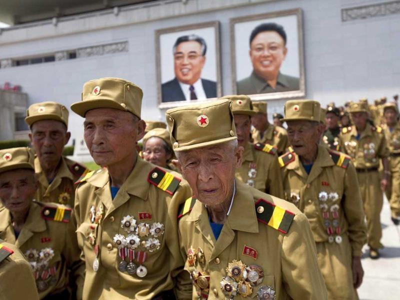 North Korean veterans of the Korean War walk under portraits of the late leaders Kim Il Sung and Kim Jong Il at the end of a mass military parade. (AP Photo)